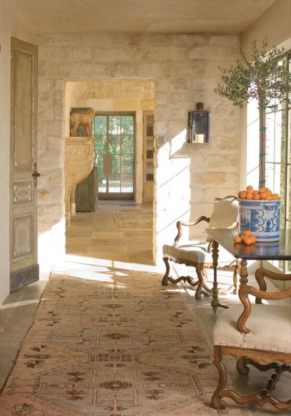 Rugged reclaimed stone walls and floor in a hall with treasures from Chateau Domingue - in Ruth Gay's exquisite French home.
