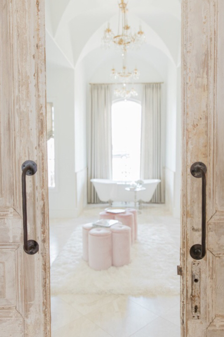 Rustic double barn doors open to an elegant French country bathroom with clawfoot tub, soaring ceilings, and a trio of chandeliers - Brit Jones. #frenchcountry #interiordesign #bathroomdesign #romanticdecor #elegantbath #luxuriousbath #barndoors #clawfoottub