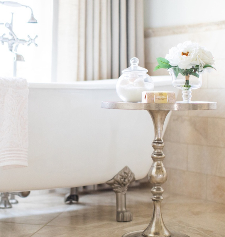 Romantic clawfoot tub in luxurious French country bathroom with travertine tile - Brit Jones. #frenchcountry #bathroomdecor #clawfoottub #romanticbathroom #interiordesign