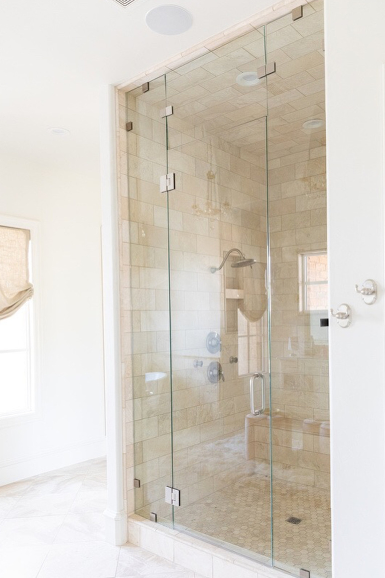 Stone tile in a shower within an elegant French country bathroom design by Brit Jones. #shower #bathroomdesign #frenchcountry #luxuriousbath