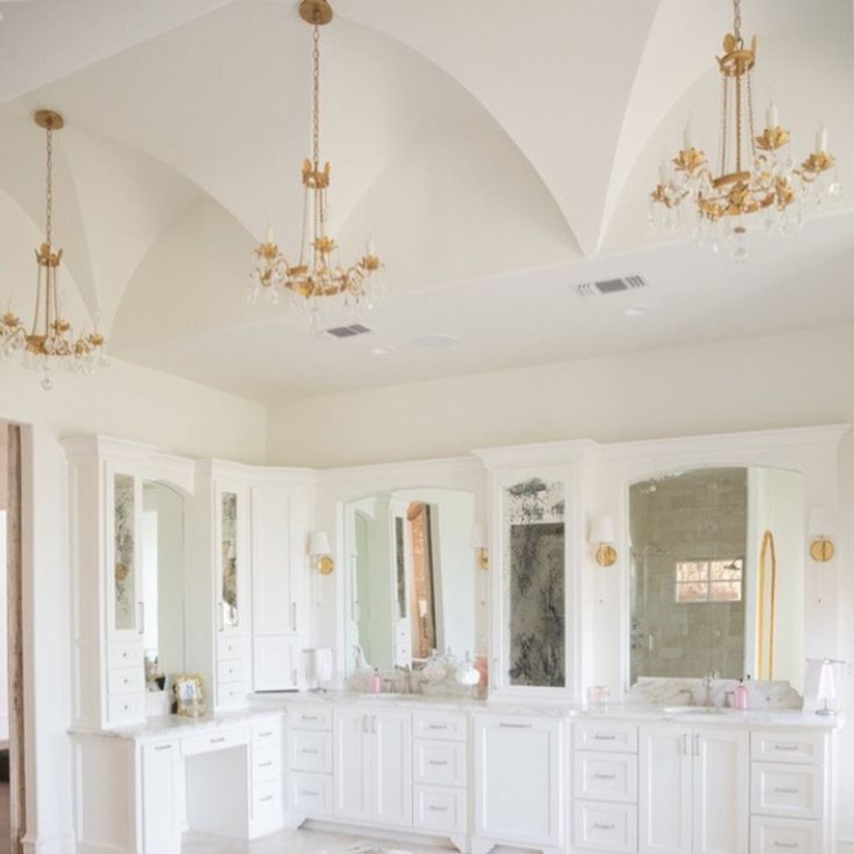 Elegant gold toned French country crystal chandeliers (Troy Viola) in a bathroom design by Brit Jones. #frenchcountry #interiordesign #bathroomdesign #chandeliers #romanticdecor