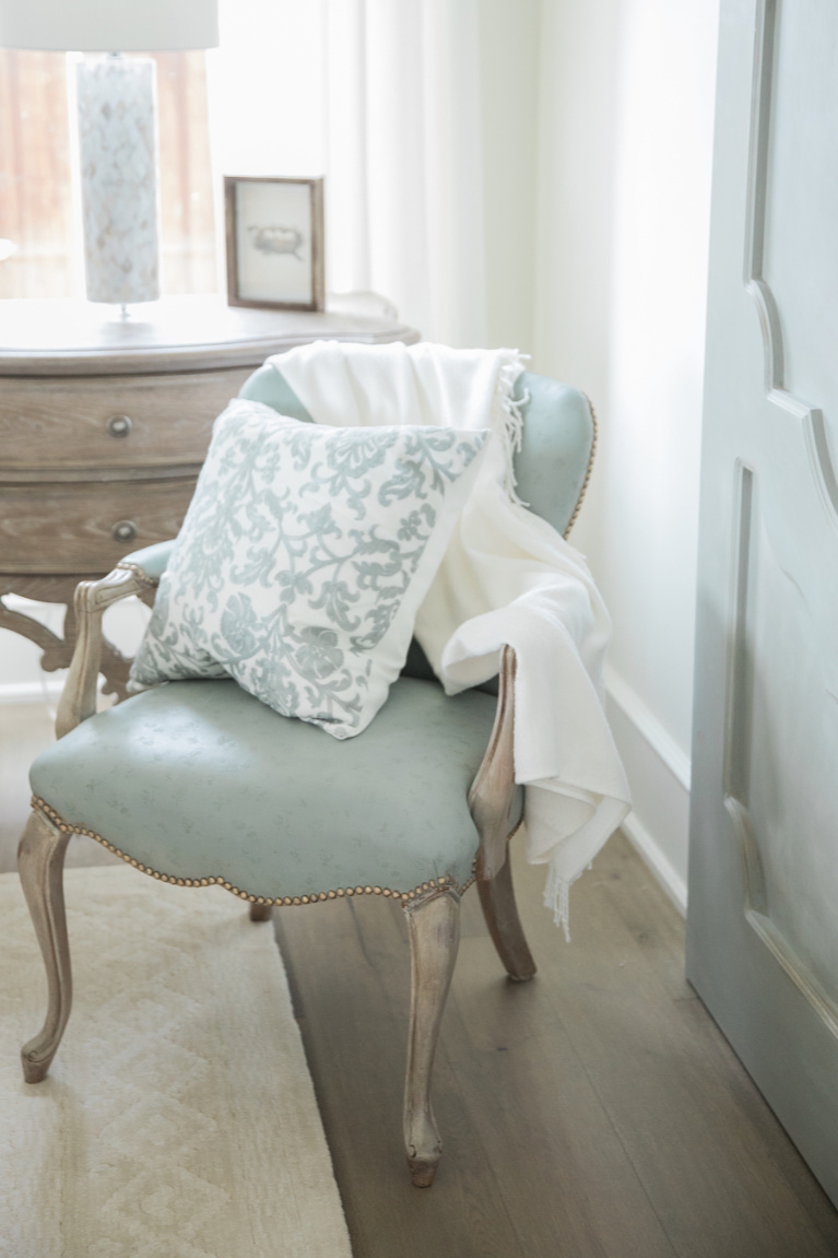 Duck egg blue upholstered arm chair and barn door in an elegant French country bedroom - Brit Jones. #duckeggblue #frenchcountry #bedroomdecor #barndoor #frenchfurniture