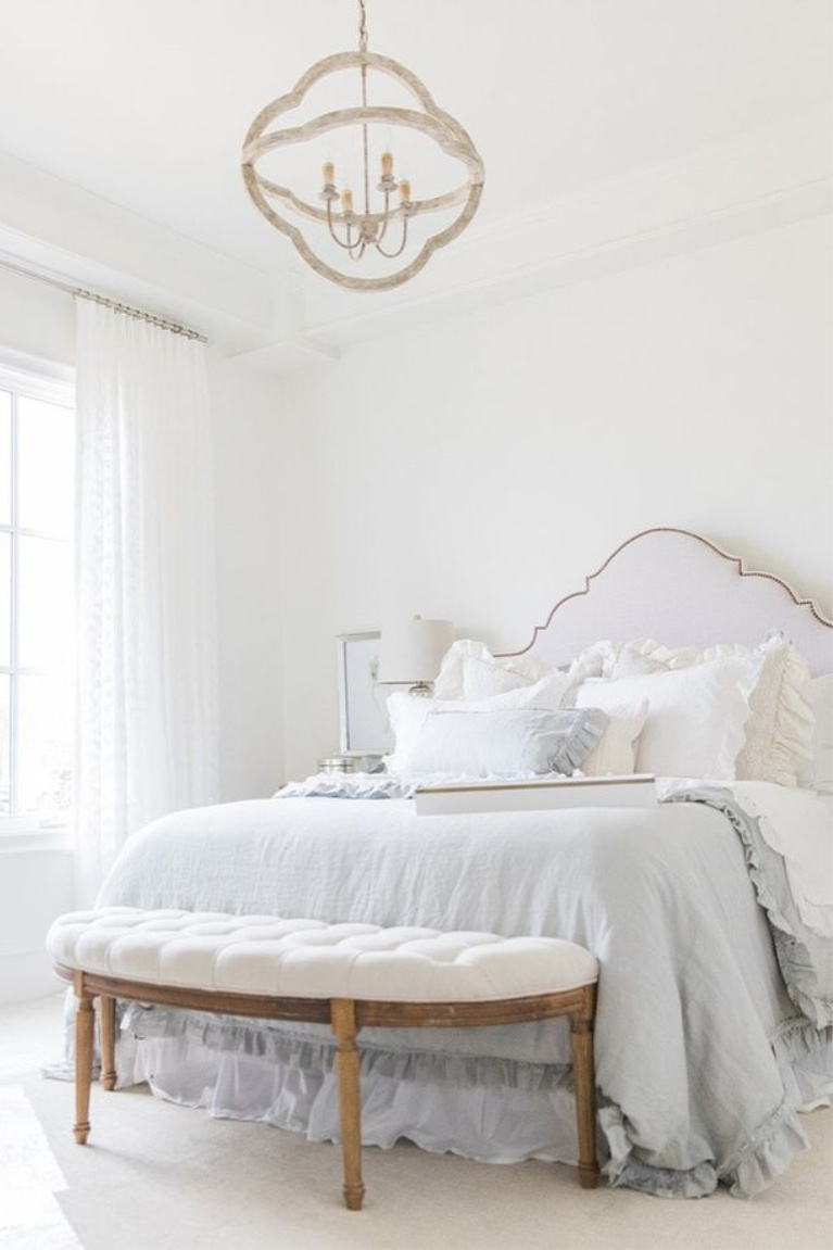 Elegant, romantic and serene French country bedroom with upholstered headboard and white drapes - Brit Jones. #interiordesign #romanticdecor #bedroomdecor #frenchcountry #whitebedrooms