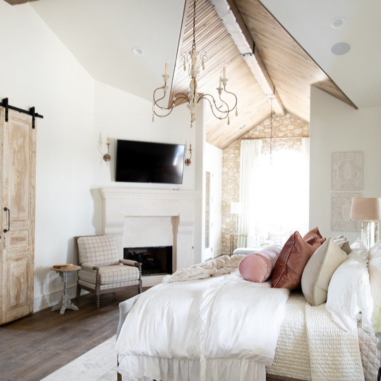 Rustic elegance in a French country bedroom with romantic decor by Brit Jones. #romanticbedrooms #interiordesign #frenchcountry #rusticdecor #barndoor #modernfrench