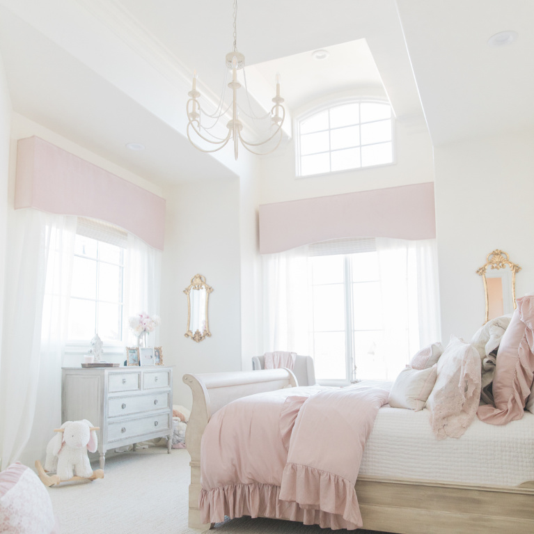 Blush pink girls bedroom with French country style and soaring ceiling with chandelier - Brit Jones Design. #frenchcountry #bedroomdecor #girlsbedroom #interiordesign #romanticdecor #pinkbedrooms #paintcolors #sherwinwilliamsalabaster