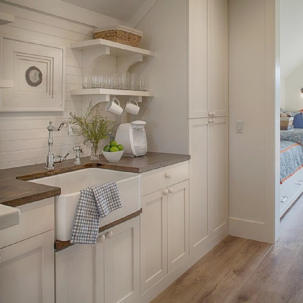 Coastal style kitchenette with custom Shaker cabinetry, farm sink, and open shelving in a charming carriage house by Lisa Furey. Explore more Coastal Cottage Inspo, Paint Colors & Whimsy Quotes Now!