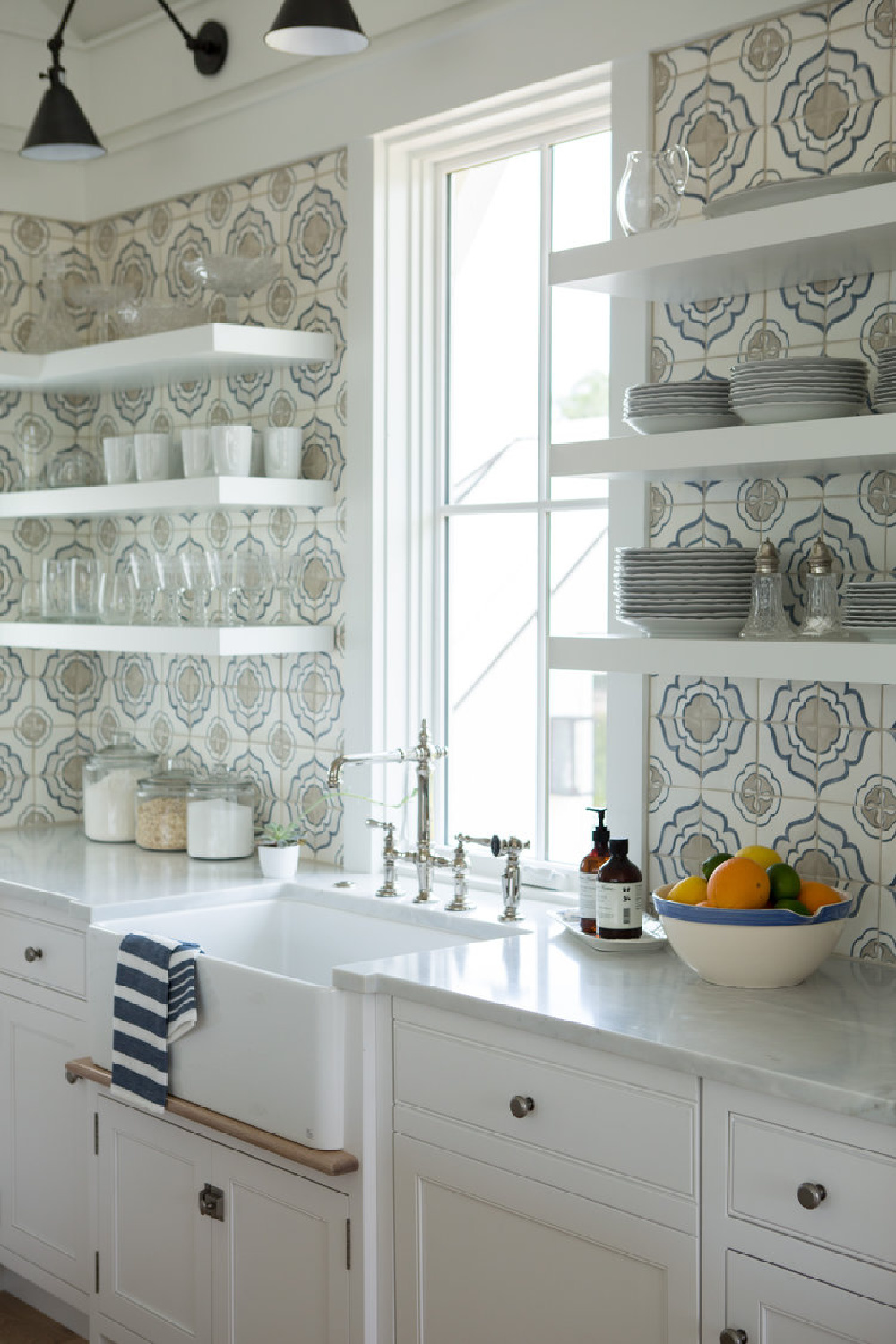 Classic white coastal cottage kitchen by Lisa Furey with handmade blue and white encaustic backsplash. Discover more Coastal Cottage Inspo, Paint Colors & Whimsy Quotes Now!