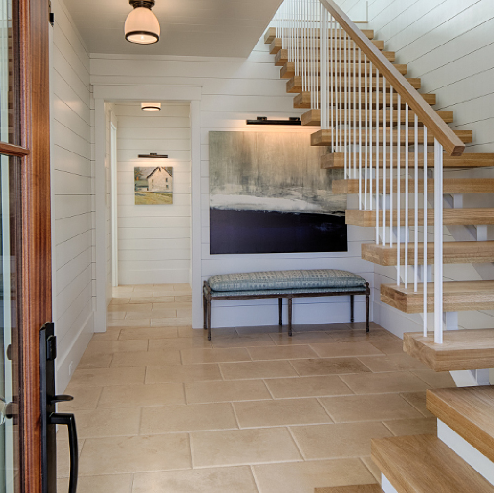 White oak hardwood flooring and floating staircase in entry.Board and batten coastal cottage in Palmetto Bluff with modern farmhouse interior design by Lisa Furey.