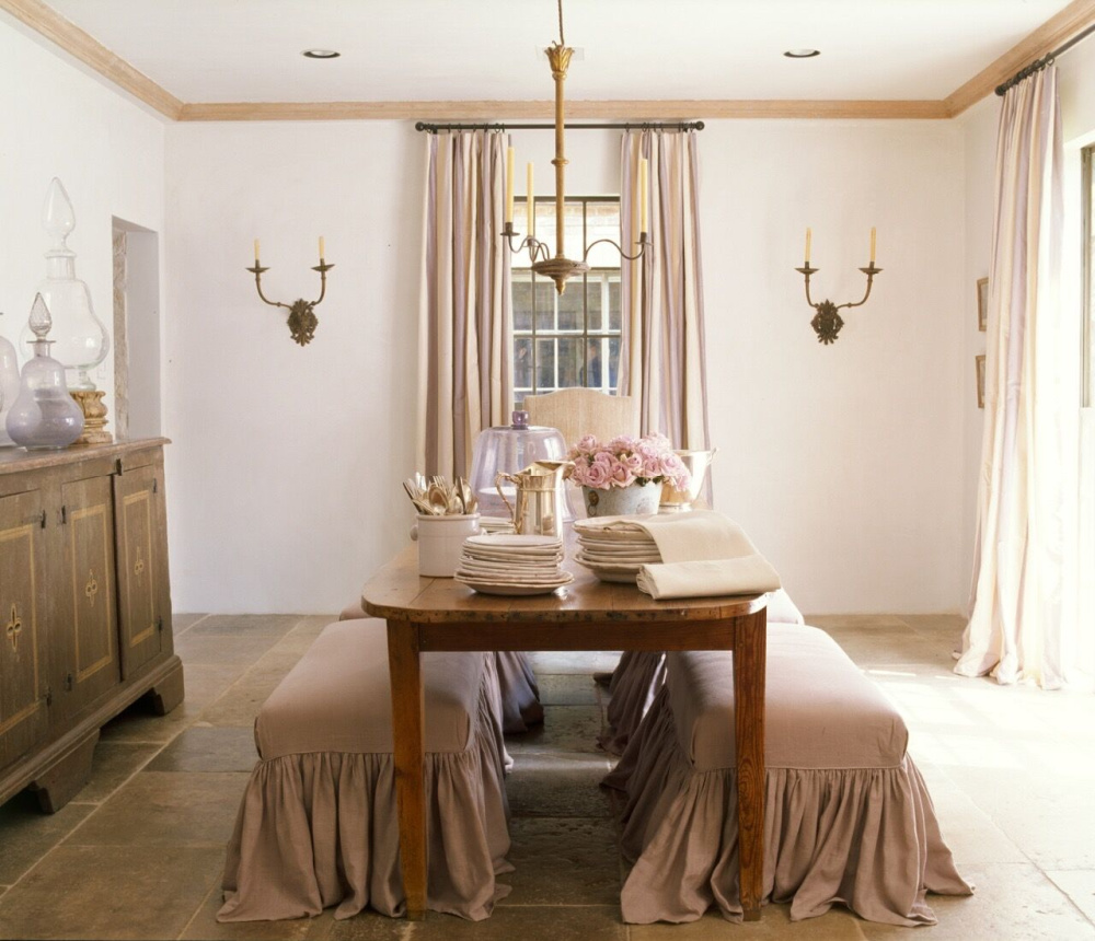 Ruth Gay's gorgeous rosy dining room with Old World French elegance. Chateau Domingue Timeless European Elegance and French farmhouse style converge in this house tour of founder Ruth Gay's home on Hello Lovely. Reclaimed stone, antique doors and mantels, and one of a kind architectural elements. #housetour #frenchcountry #frenchfarmhouse #europeanfarmhouse #chateaudomingue #rusticdecor #pamelapierce #elegantdecor #diningroom #romantic