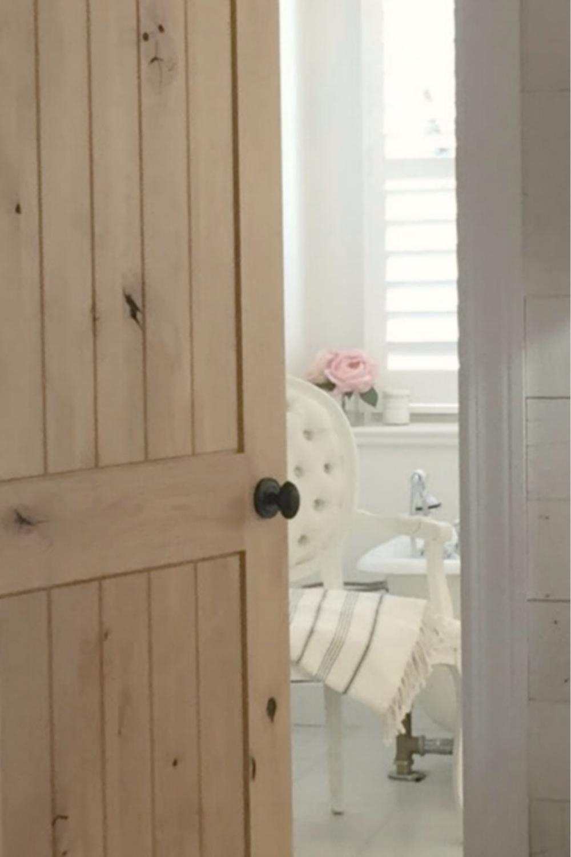 White Country French bathroom with knotty alder door - Hello Lovely Studio. #alderdoor #europeancountry #bathroomdesign