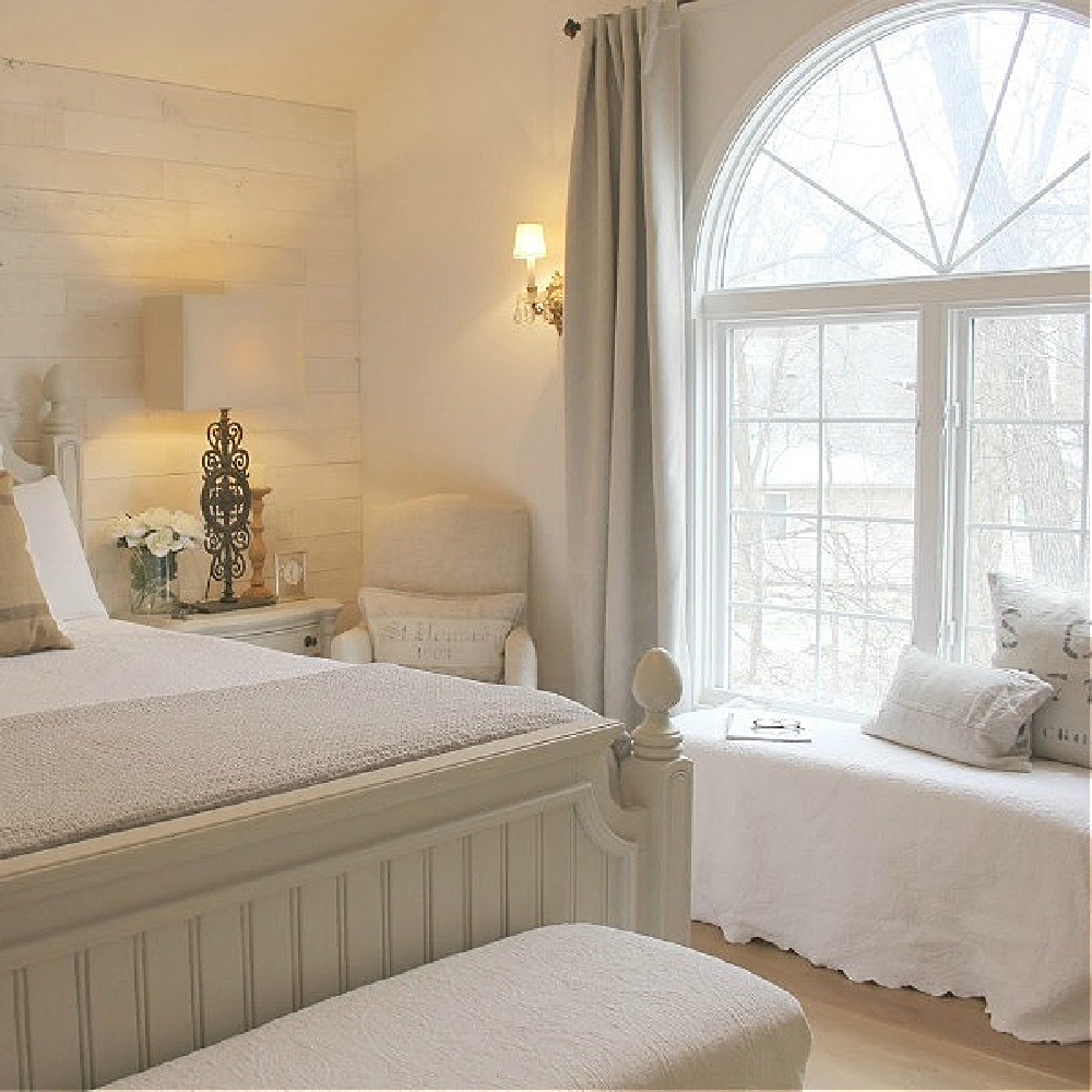 Serene white French country bedroom with bench at large fan window - Hello Lovely.