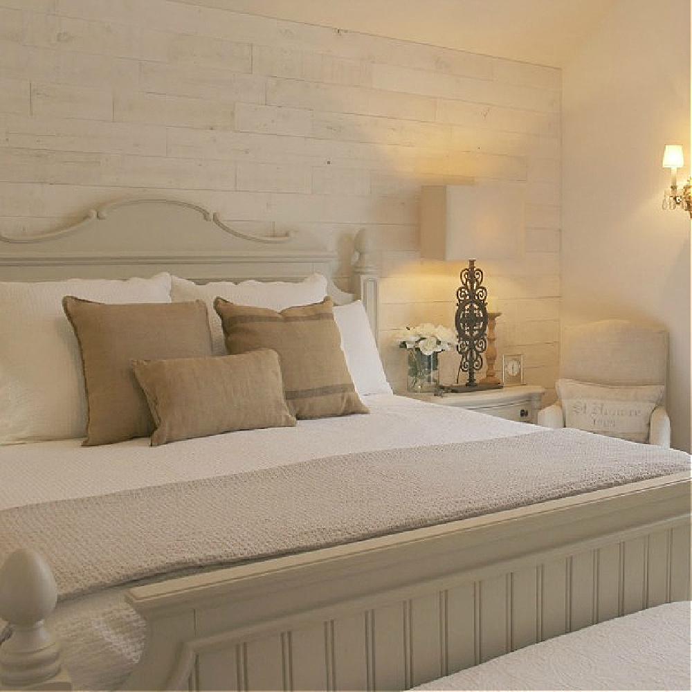 Pale neutral Country French bedroom with Stikwood Hamptons accent wall, beadboard panel bed, and burlap throw pillows on white linens - Hello Lovely Studio.