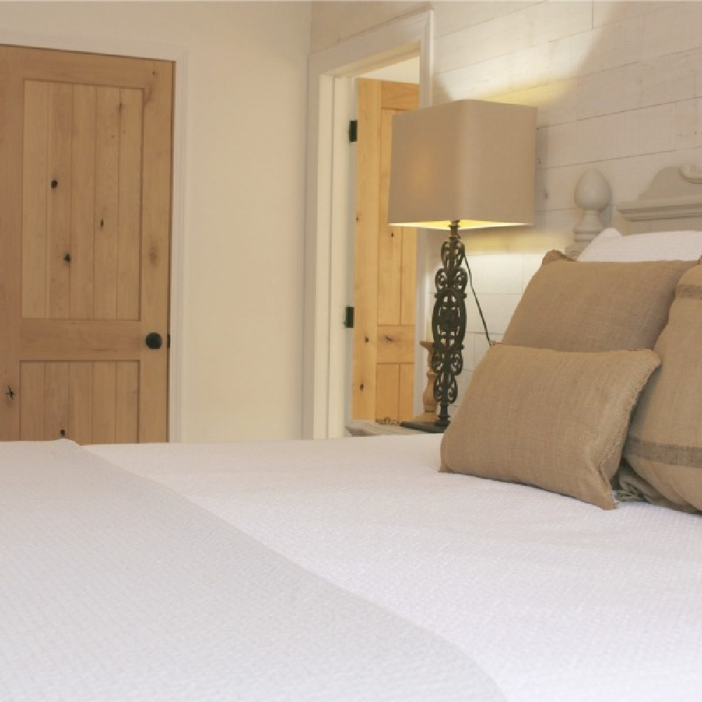 European country style bedroom with knotty alder interior doors and white bedding - Hello Lovely. #alderdoors
