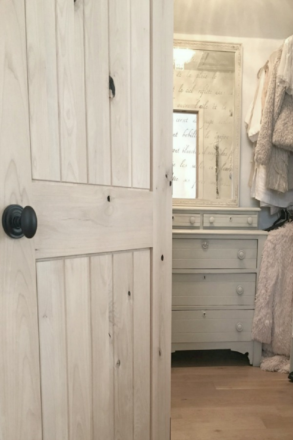 Rustic knotty alder door to my closet with antique painted dresser and stenciled mirror - Hello Lovely Studio.