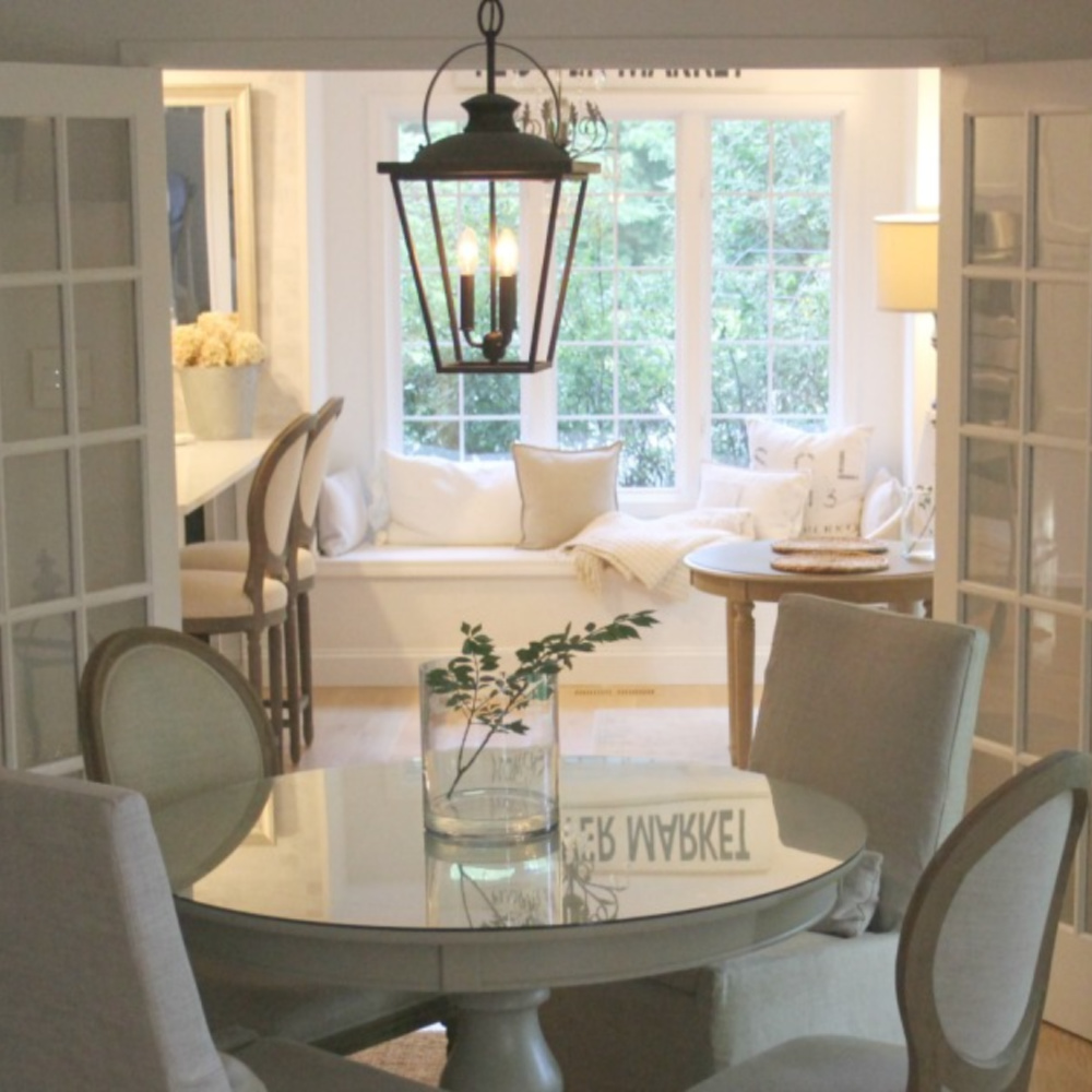 Cozy European country style dining room with vintage French doors leading to kitchen with window seat - Hello Lovely.