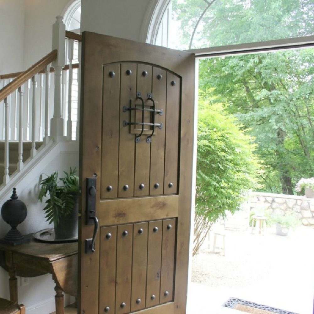 Rustic knotty alder exterior door with walnut stain and speakeasy in our European country cottage entry - Hello Lovely.