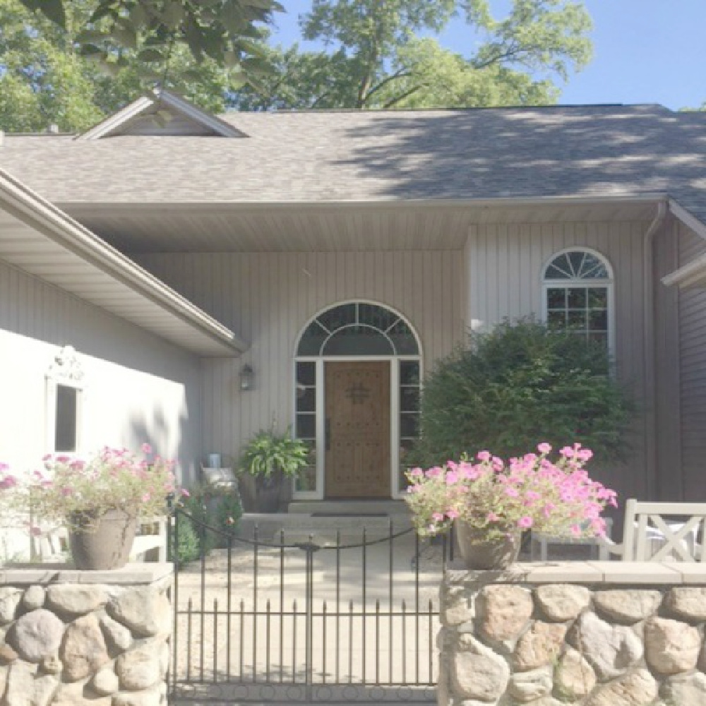 Hello Lovely Studio's home exterior with rustic stone walled entrance and knotty alder front door.