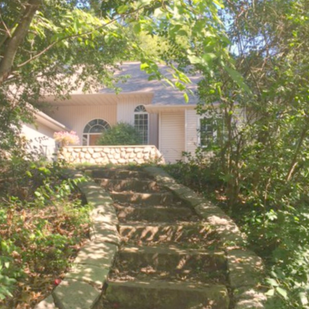 European country cottage exterior with stone steps leading to courtyard entrance with stone wall - Hello Lovely Studio.