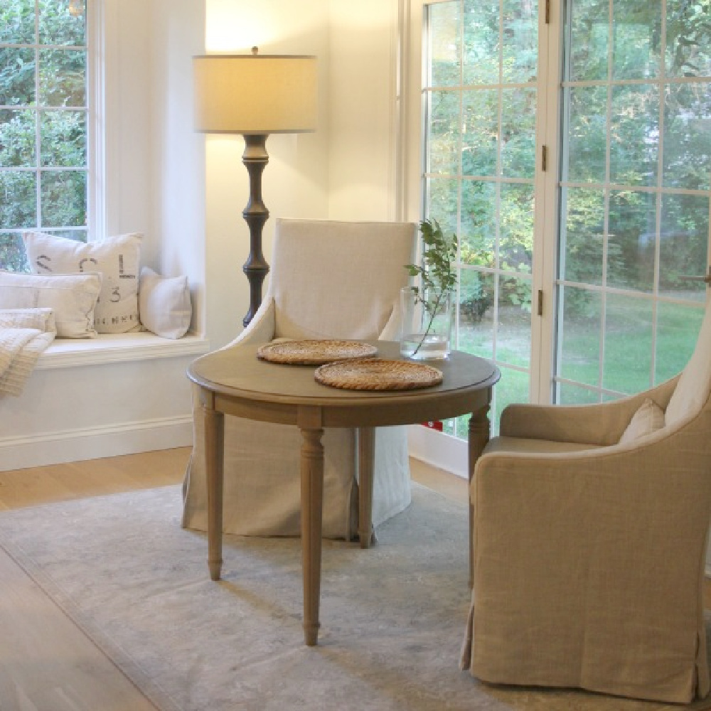 Belgian linen slope arm dining chairs in our breakfast nook with window seat - Hello Lovely.