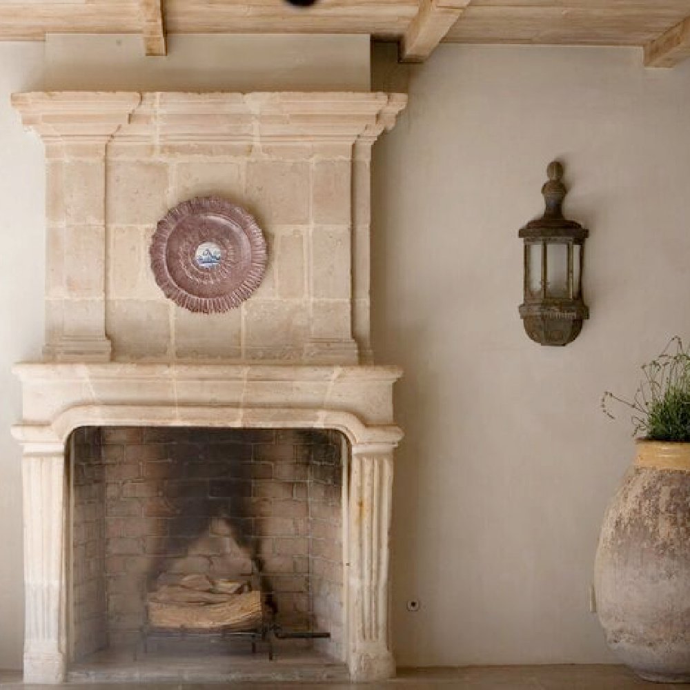 Chateau Domingue antique limestone fireplace with fluted detail, French confit pot, and reclaimed lantern in a serene interior within Ruth Gay's breathtaking Houston home. #oldworld #limestonefireplace #frenchfireplace #antiquefireplacesurround