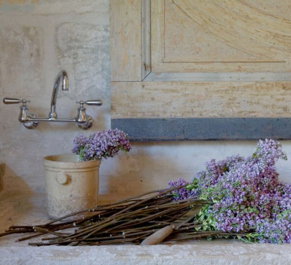 Pale tones of rugged stone, antiques, earthenware, and age sing with French lavender in Ruth Gay's Old World Houston home - Chateau Domingue.