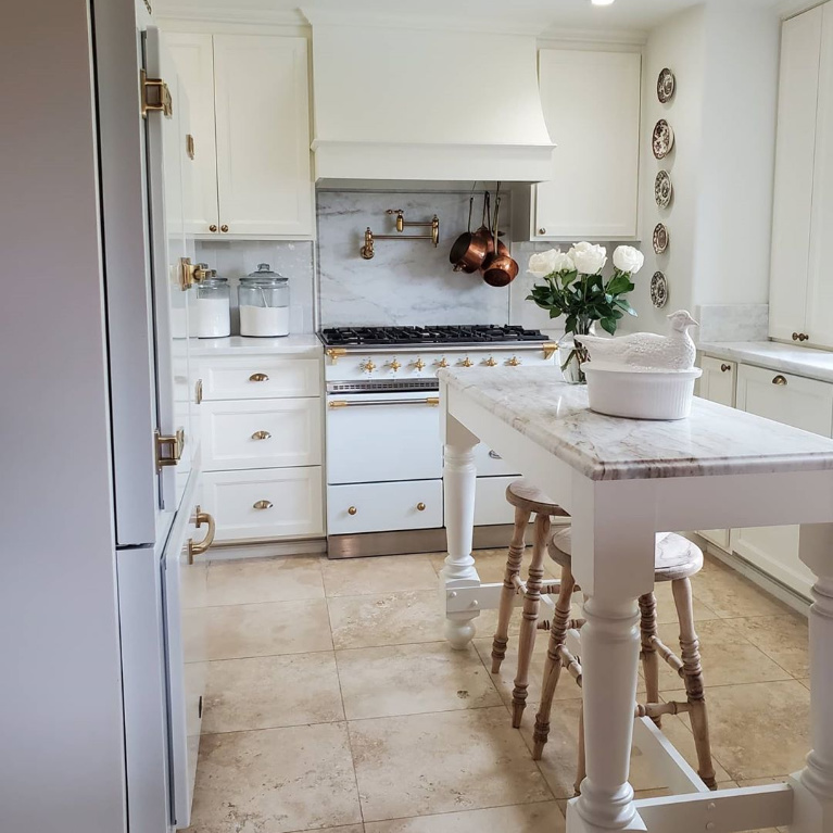 White French kitchen with Lacanche range, island and rustic wood farmhouse stools - The French Nest Co Interior Design. #whitekitchen #kitchendesign #frenchkitchens #lacanche #frenchcountry #interiordesign #modernfrench