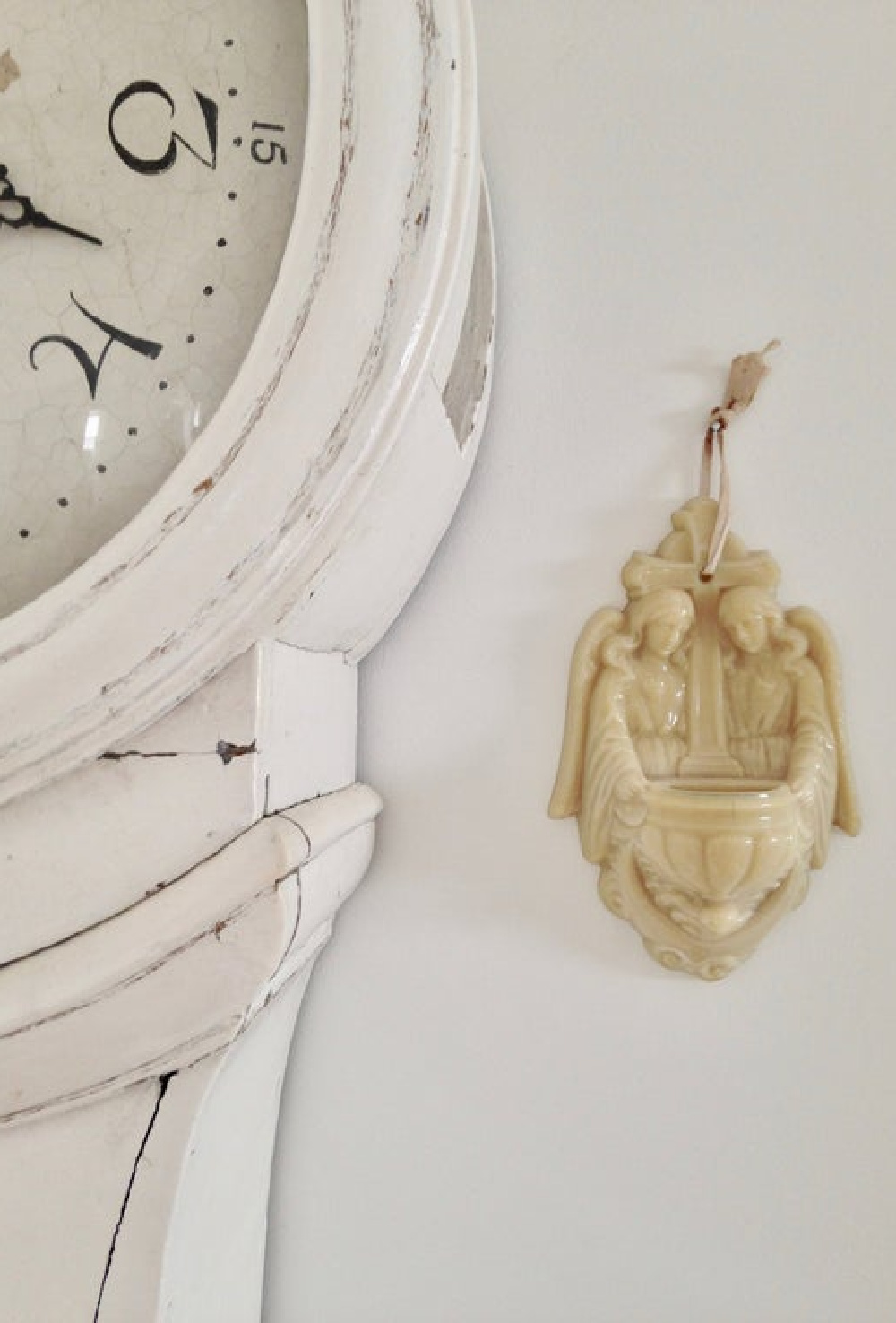 Antique French holy water font near white Swedish mora clock - My Petite Maison.