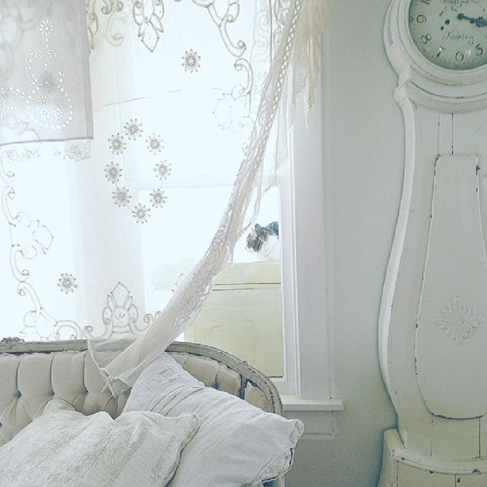 White Swedish Mora clock and tufted velvet settee in a cottage living room with serene vibe by My Petite Maison.