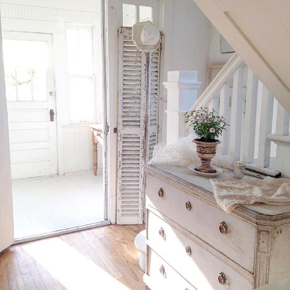 All white French Nordic cottage entry with Swedish antiques, rustic shutters, and white painted floors - My Petite Maison.