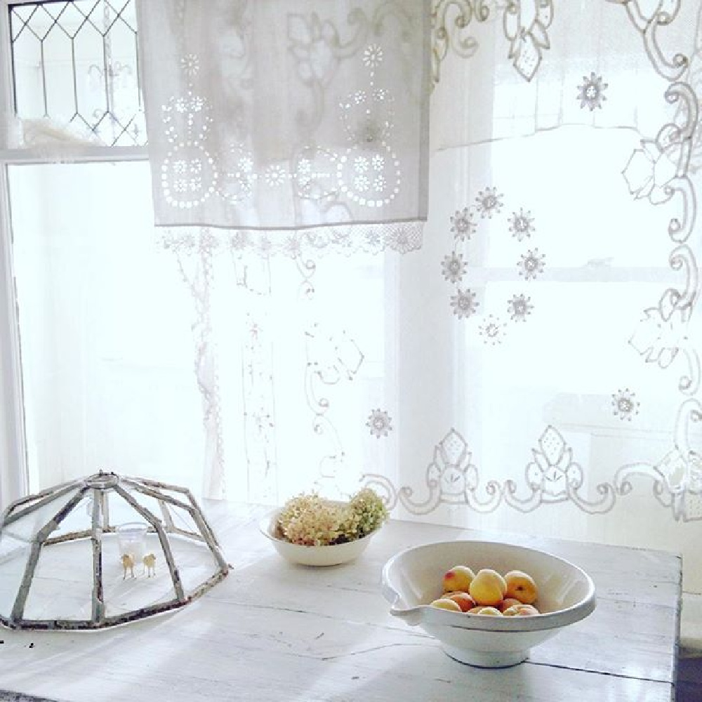 French antiques and vintage kitchenwares in an all white country kitchen with sheer lace curtains - My Petite Maison.