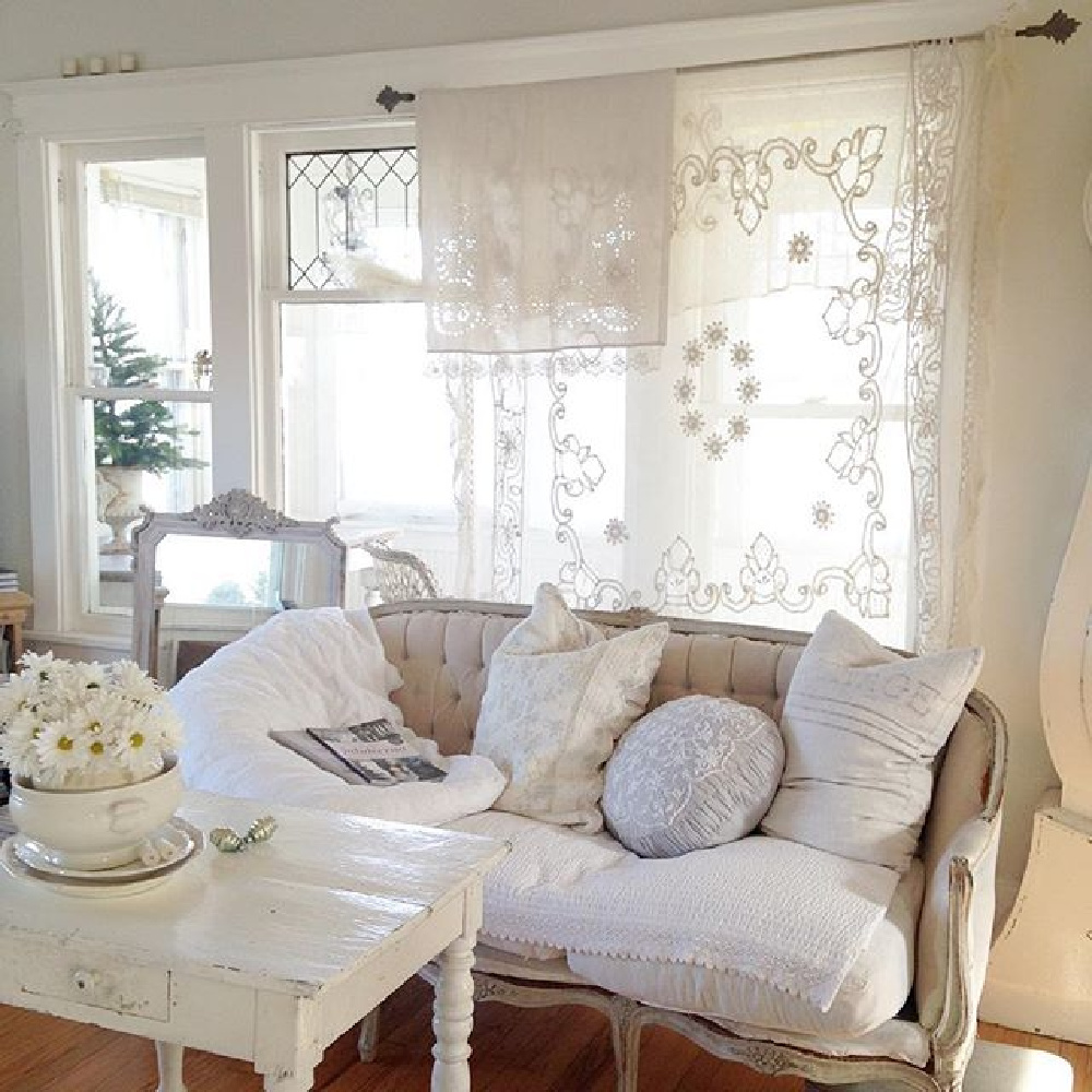 All white Swedish and French decor in a cottage with sheer lace curtains and velvet settee - My Petite Maison.