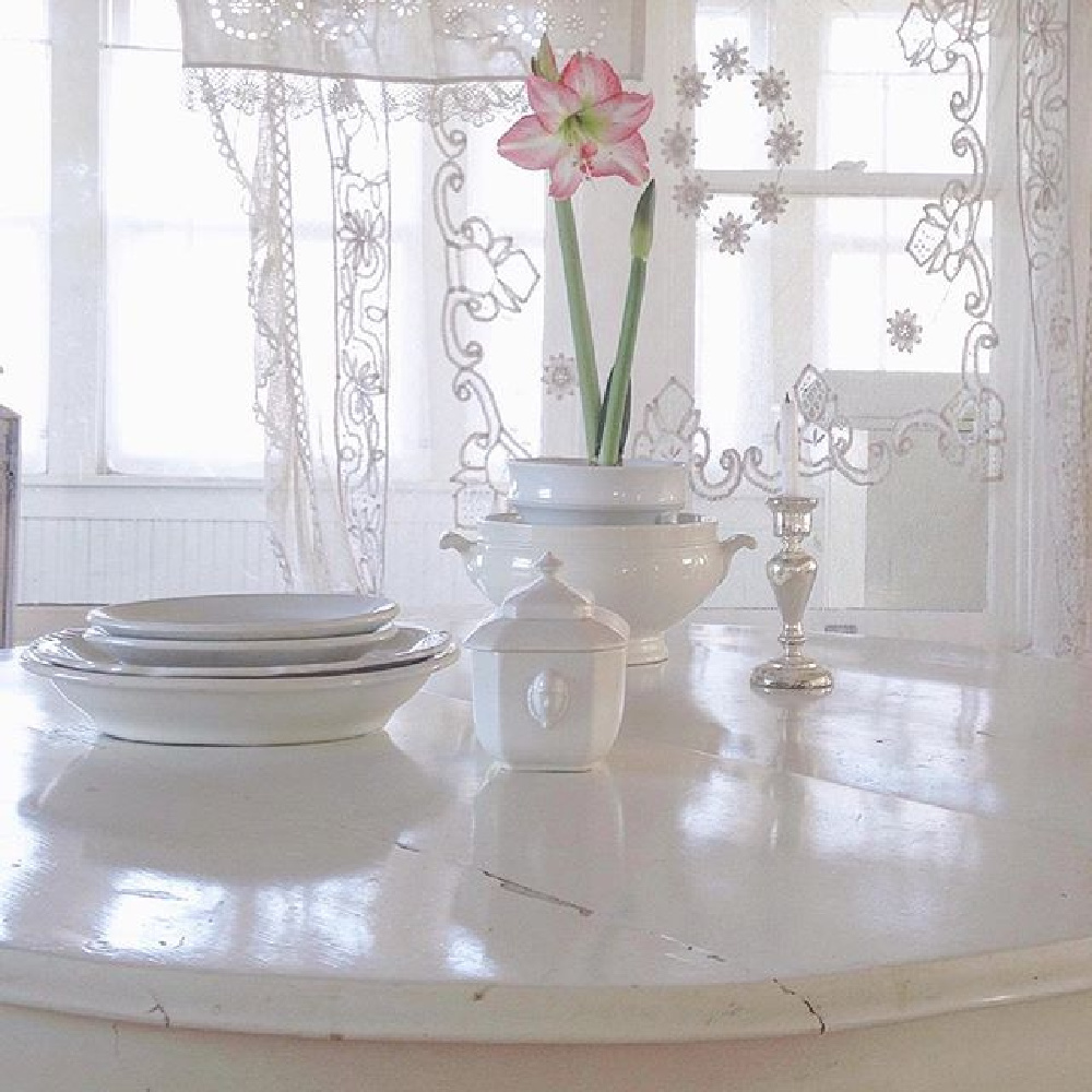 Vintage French ironstone, all white decor, and sheer lace curtain panels in a serene Nordic French cottage by MyPetiteMaison.