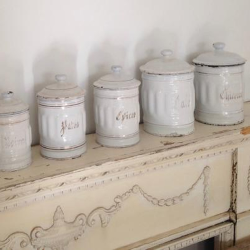 Vintage French white canisters on a fireplace mantel styled by @mypetitemaison. #frenchvintage #frenchkitchendecor