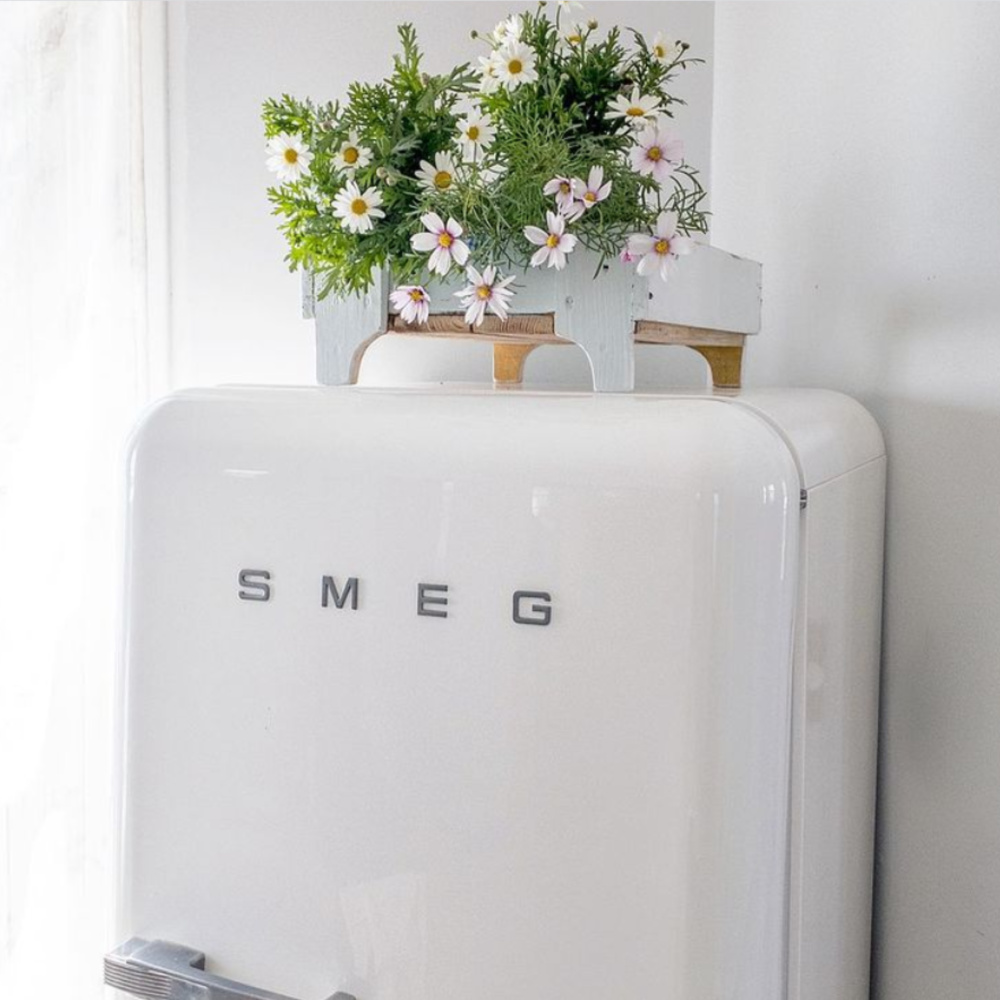 Adorable white Smeg refrigerator with daisies displayed in an old Swedish blue painted crate - @mypetitemaison. #frenchnordic #nordicfrench #frenchkitchen #vintagekitchen