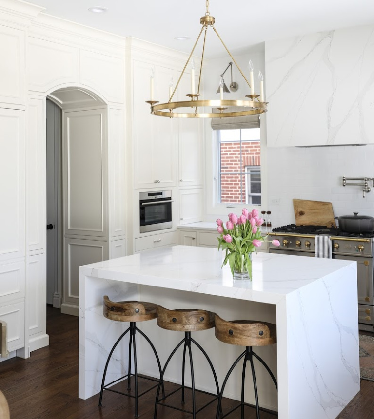 Simple yet sophisticated white elegant kitchen with brass hardware, waterfall island, and farm sink - Park and Oak. #kitchendesign #classickitchen #whitekitchen #waterfallisland ##farmsink #elegantkitchen