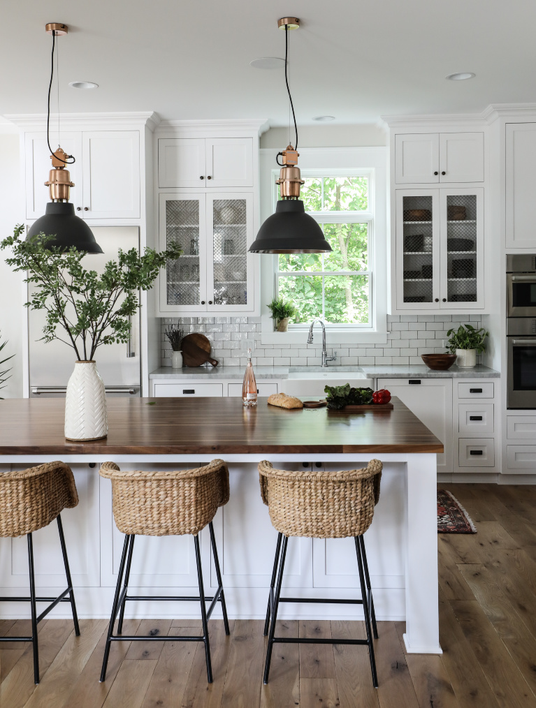 Simple yet sophisticated white modern farmhouse kitchen with wood topped island and rattan stools - Park and Oak. #kitchendesign #classickitchen #whitekitchen #coastalkitchen #whiteoak #modernfarmhouse