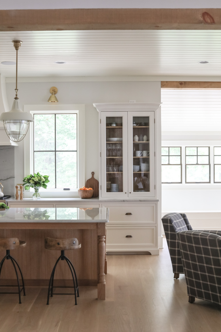 Simple yet sophisticated white coastal kitchen with contrasting wood tone island in a lake house - Park and Oak. #kitchendesign #classickitchen #whitekitchen #coastalkitchen #whiteoak #modernfarmhouse