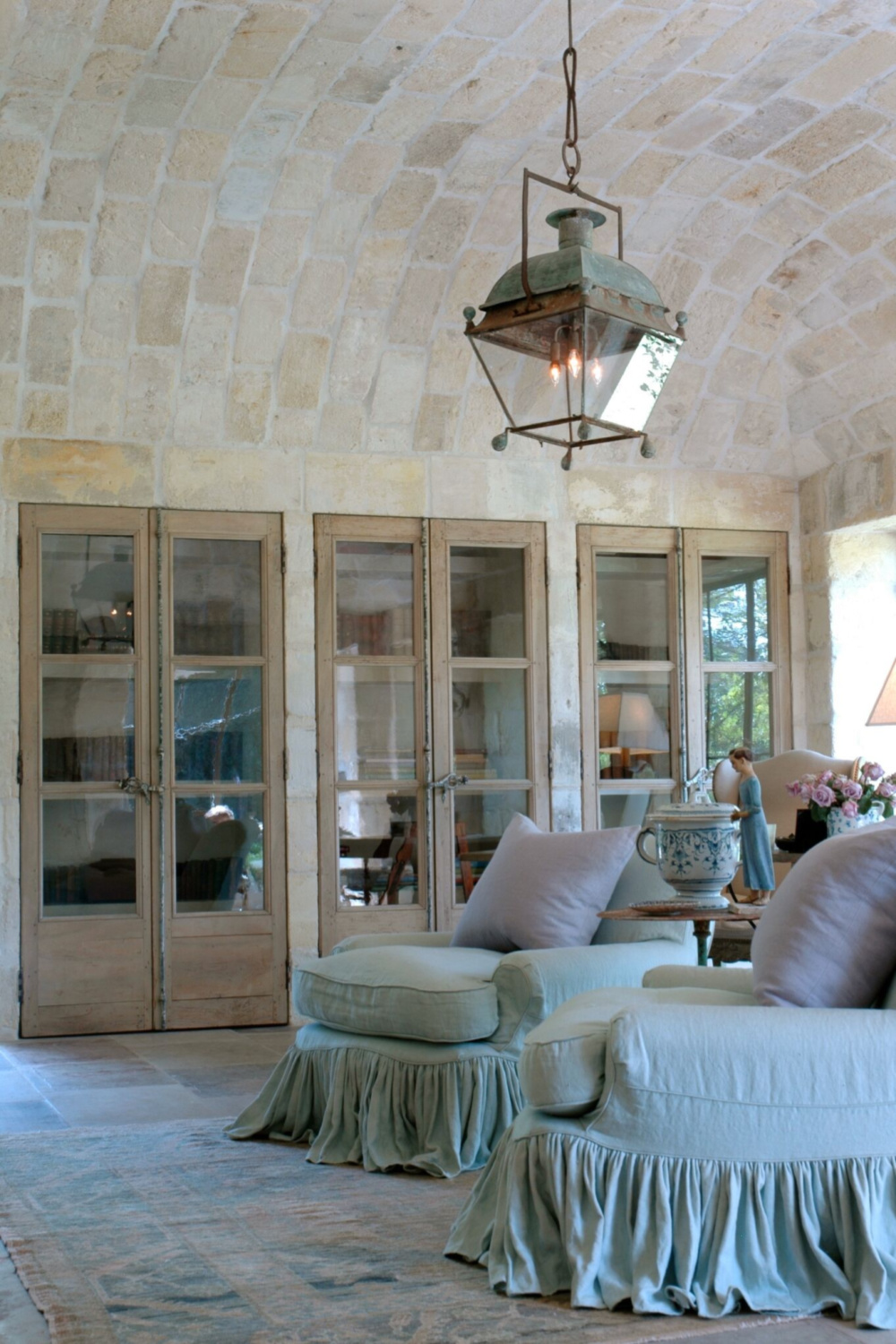 Three pairs of 18th century French doors, barrel vaulted ceiling clad in 17th century stone from a French Vineyard, and blissful upholstered pieces grace Ruth Gay's office.#chateaudomingue #antiques #frenchcountry #frenchfarmhouse #lantern #limestone #oldworld