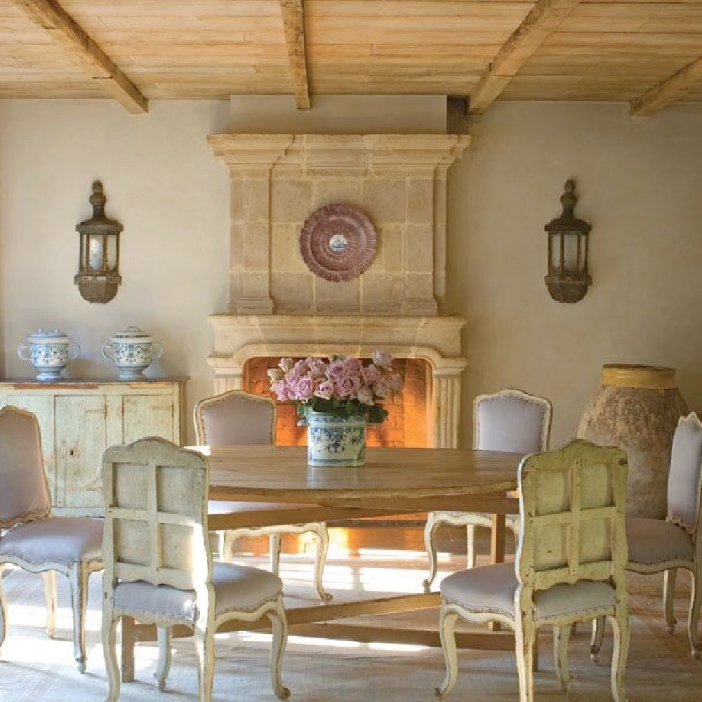 Country French dining room with rustic wood ceiling (reclaimed from Europe by Chateau Domingue), stone floors, and exquisite antique stone fireplace.