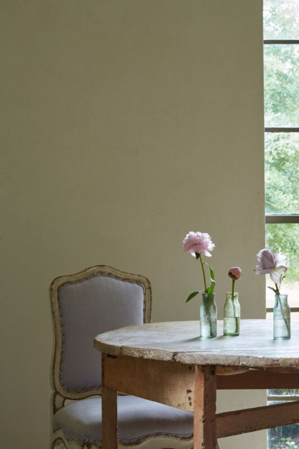 Serene, understated French country dining chair and rustic farm table with simple glass bottles used as vases - Chateau Domingue.