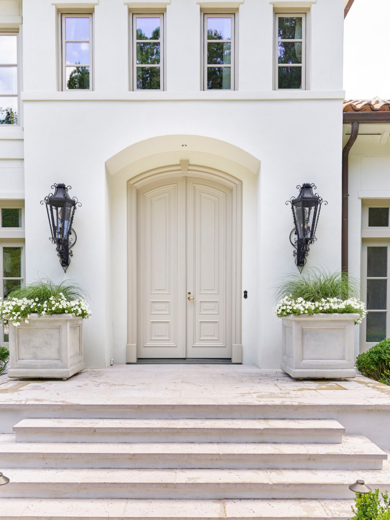 Breathtaking front door and entry to traditional style white stucco mansion in Buckhead. The 2020 Southeastern Designer Showhouse 'Villa Flora' is painted Benjamin Moore Seapearl and trim is Benjamin Moore Pashmina. #paintcolors #seapearl #benjaminmooreseapearl #pashmina #benjaminmoorepashmina #houseexteriors #housecolors