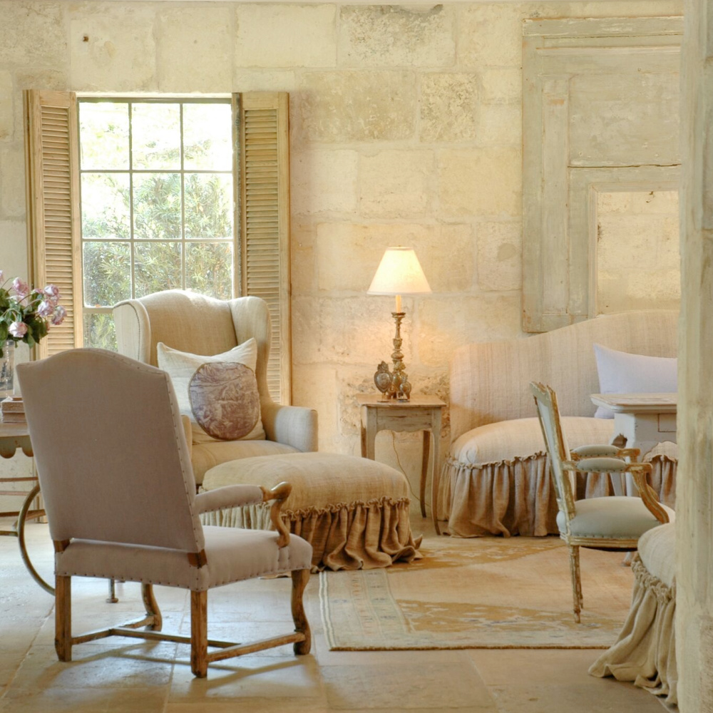 Sunny limestone, chalky hues, linen upholstered furniture with ruffled skirts, and reclaimed stone mix charmingly in a living room with French flair - Chateau Domingue. #countryfrench #interiordesign #livingroom #oldworld