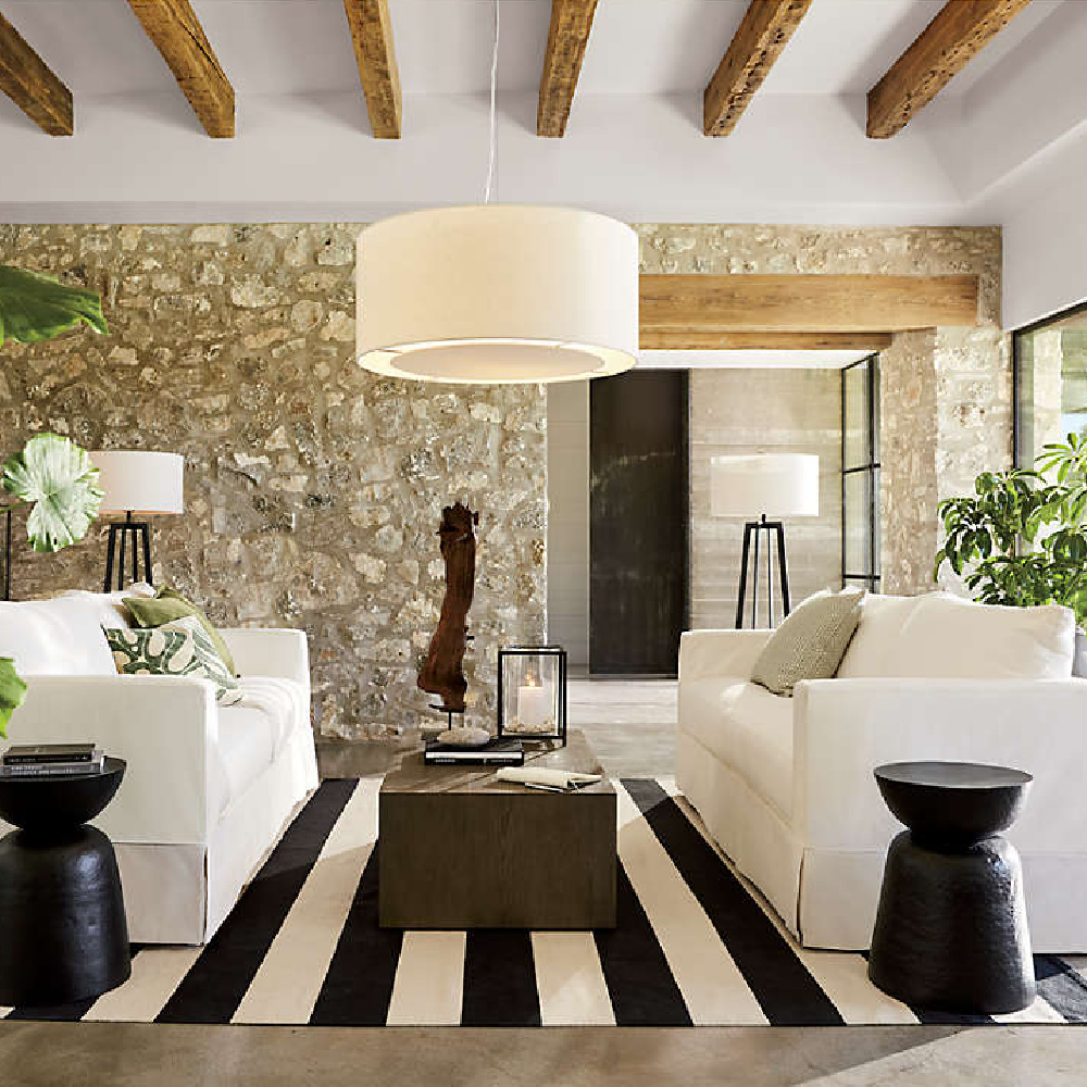 Charming rustic modern family room with beamed ceiling, stone wall, and Willow modern slipcovered sofa - Crate & Barrel. #modernrustic #familyroom #slipcoveredsofas