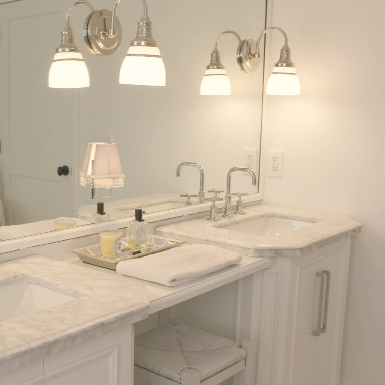 Traditional freestanding white single vanity with makeup counter in our French country bathroom with calacatta like porcelain tile. #hellolovelystudio #bathroomdesign #whitevanities #carraramarble #makeupcounter #hisandhervanities