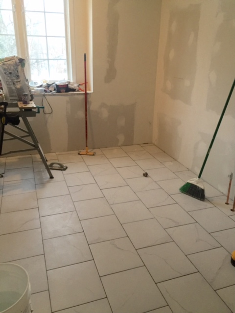 before pic during Hello Lovely's master bathroom renovation when calacatta-look porcelain floor tile installed.