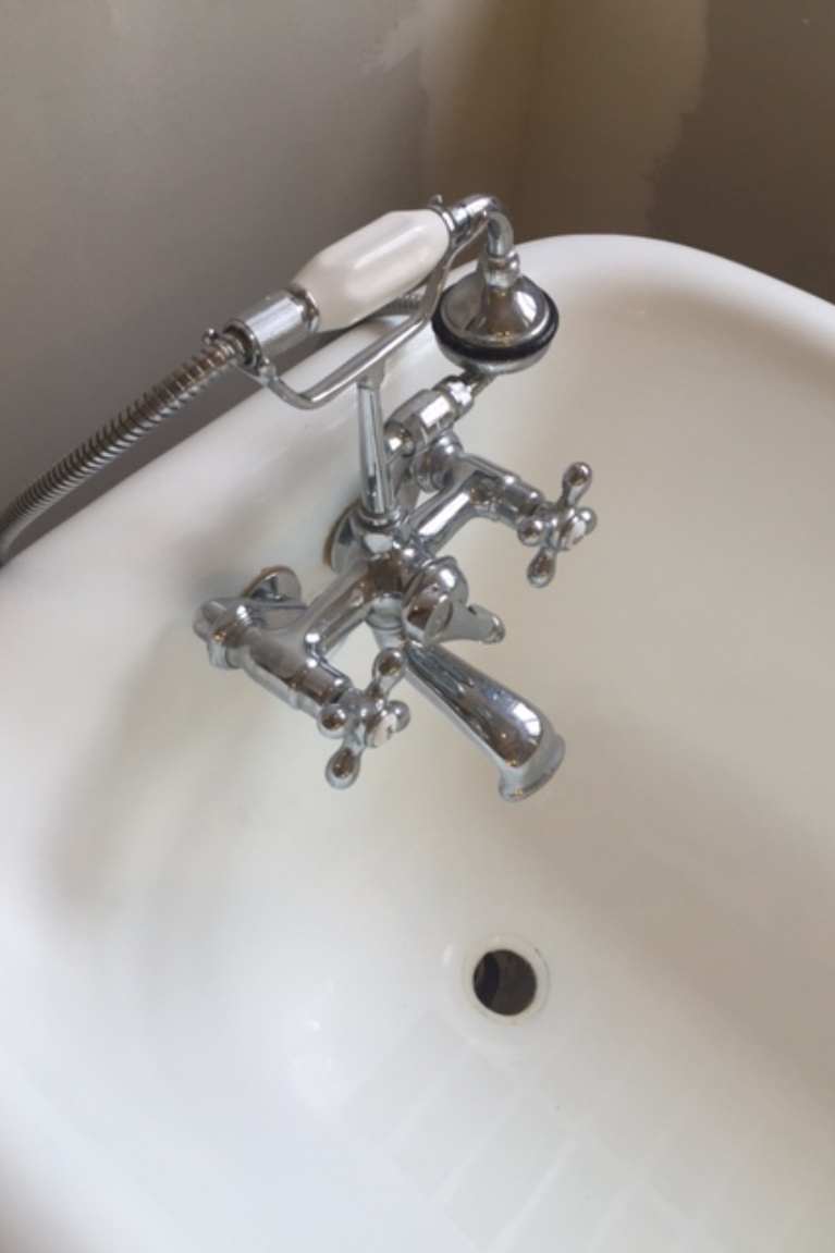 Detail of clawfoot tub bath faucet and handheld shower - Hello Lovely Studio. #clawfoottub #bathfaucet #vintagestyle