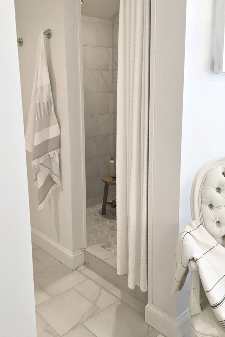 White French country bathroom with calacatta-look porcelain tile on shower walls and marble mosaic on floor. #hellolovelystudio #bathroomdesign #showertile #frenchcountry #whitebathrooms #herrinbone #marblemosaic