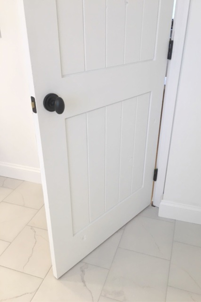 White painted alder door in our bathroom - hardware is Helmsley egg knob. Tile is calacatta-look porcelain tile. #bathroomdecor #hellolovelystudio #whitedoors