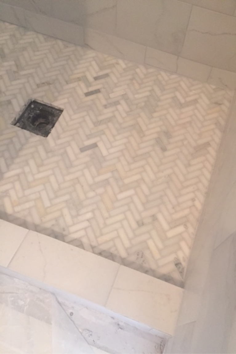 Herrinbgone marble mosaic tile on floor of our shower during renovation of master bath. #hellolovelystudio #herringbone #showertile #showerfloor #marblemosaic #floortile