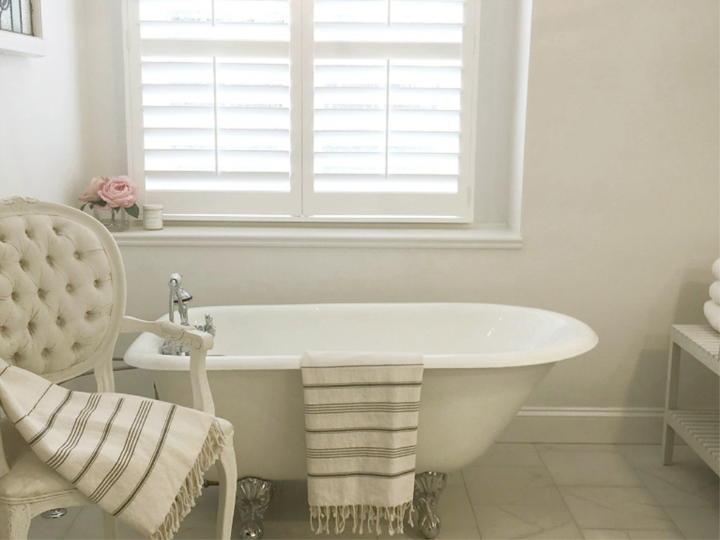 Clawfoot tub, French chair, and stripe Turkish towels in white French country bathroom by Hello Lovely Studio. #bathroomdesign #frenchcountry #hellolovelystudio #clawfoottub #plantationshutters #whitebathroom #frenchbathroom #vintagestyle